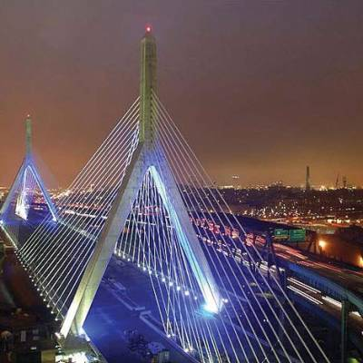 a large bridge lit up at night with Leonard P. Zakim Bunker Hill Memorial Bridge in the background