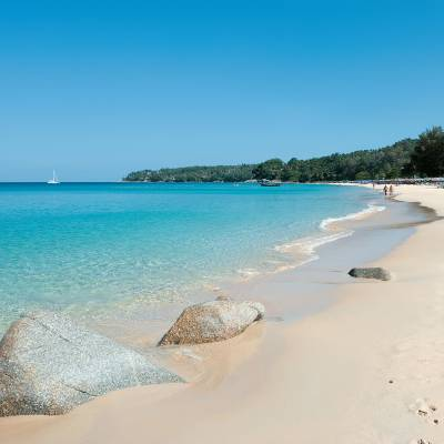 a sandy beach next to a body of water