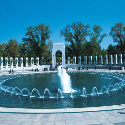 a man in a pool of water with National World War II Memorial in the background