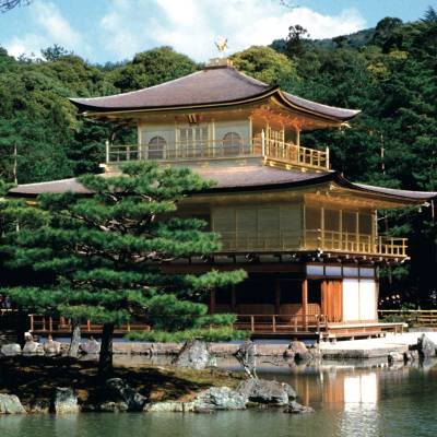 a small house in a body of water with Kinkaku-ji in the background