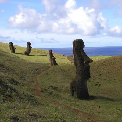 a group of people walking on a grassy hill with Easter Island in the background
