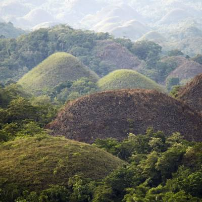 a view of a large mountain in the background with Chocolate Hills in the background