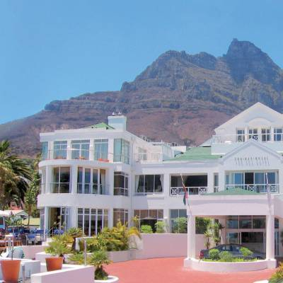 a large white building with a mountain in the background