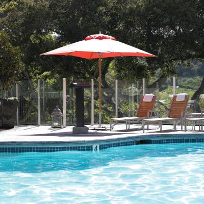 a red umbrella next to a pool of water