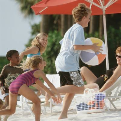a group of people sitting at a beach umbrella in the sand