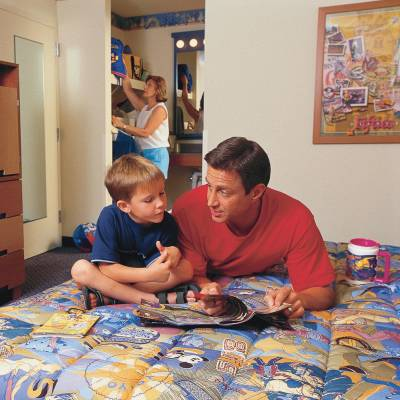 a man and a little boy sitting on a bed