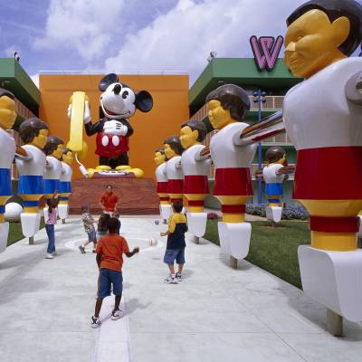 a group of people sitting around a fire hydrant with Disney's Pop Century Resort in the background
