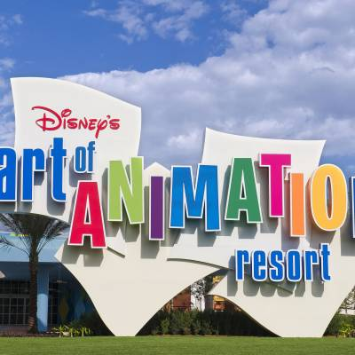 a close up of a sign with Disney's Art of Animation Resort in the background