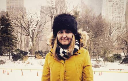 a person wearing a yellow jacket standing in the snow