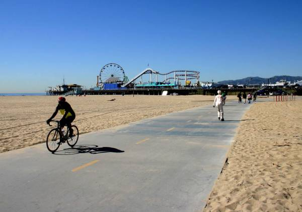 a person riding a bicycle on a sandy beach