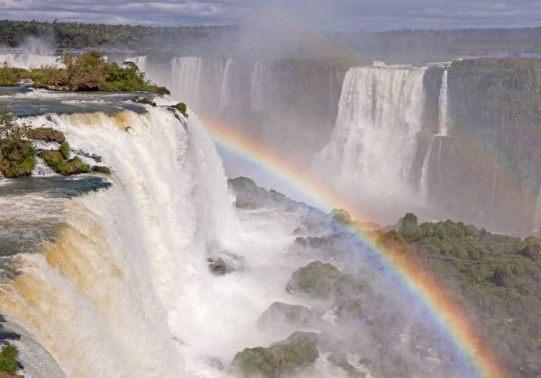 a large waterfall coming out of the water with Iguazu Falls in the background