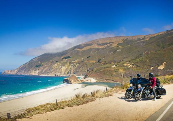 a group of people riding a motorcycle on a beach