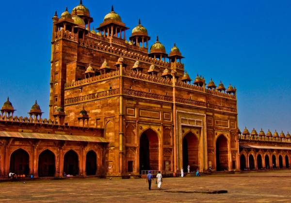 a large stone building with Fatehpur Sikri in the background
