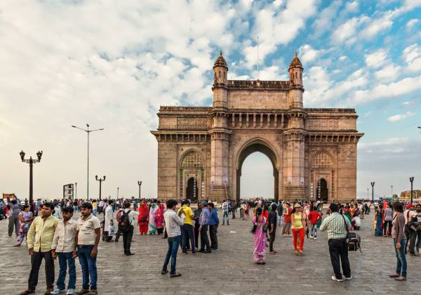 a group of people walking in front of a crowd with Gateway of India in the background