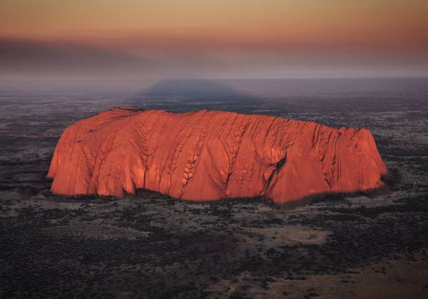 a sunset over a body of water with Uluru in the background