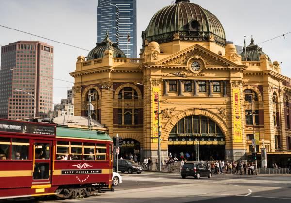 A burgundy tram in front of Flinder Street Station, Melbourne