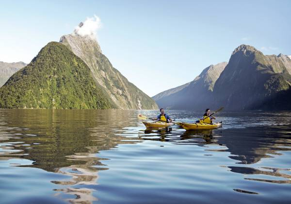 a small boat in a body of water with Milford Sound in the background