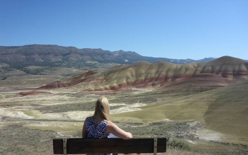 a person sitting on a bench in front of a mountain