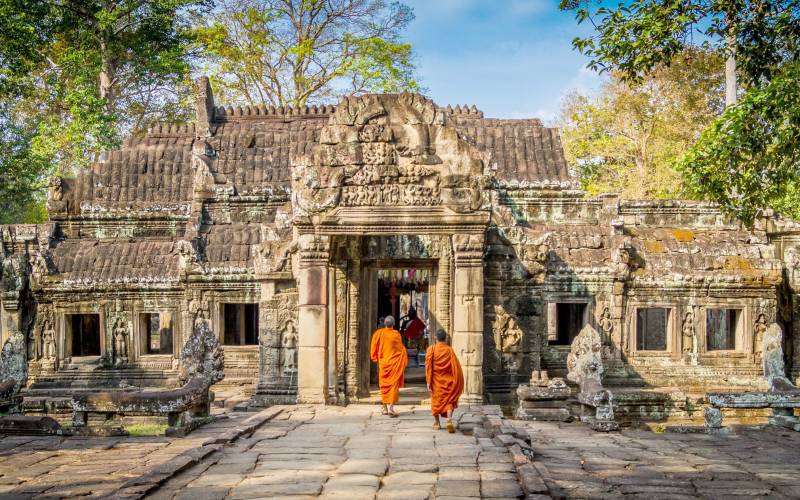 a person standing in front of a stone building with Angkor Wat in the background
