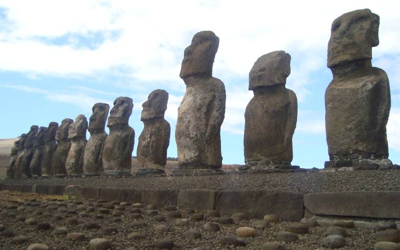 a group of people on a rock with Easter Island in the background