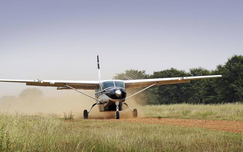 a small plane sitting on top of a grass covered field