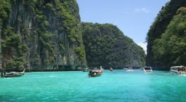 ein kleines Boot in einem Gewässer umgeben von Bäumen mit Phi Phi Inseln im Hintergrund
