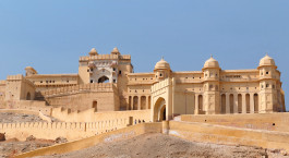 a large white building with Amer Fort in the background