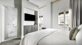 ein Hotelzimmer mit Bett und Blick in die Kamera