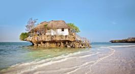 ein Haus an einem Strand in der Nähe eines Gewässers