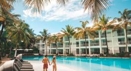 ein Strand mit einer Palme vor einem Pool von Wasser