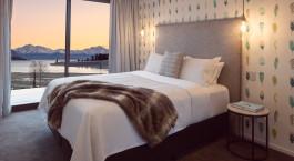 Doppelbett mit Blick aus dem Fenster im Ranginui Bed & Breakfast in Neuseeland