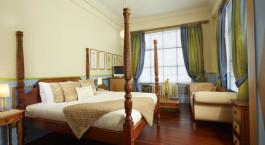 ein Schlafzimmer mit einem Bett und einem Stuhl in einem Zimmer