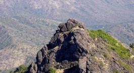 ein felsiger Hügel mit einem Berg im Hintergrund