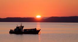 ein Sonnenuntergang hinter einem Boot auf einem Gewässer