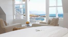 ein großes weißes Bett neben einem Fenster