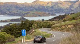 Auto auf malerischer Bergstrau00dfe vor Bergen und See in Akaroa, Neuseeland