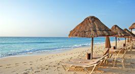 eine Gruppe von Liegestühlen auf einem Sandstrand sitzen