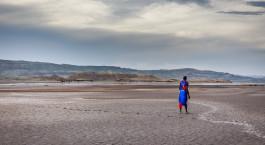 ein kleiner Junge, der einen Drachen am Strand fliegt