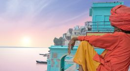 Hindu sadhu baba in meditation at the Ganges river bank at sunrise with view of a wooden boat on river Ganga
