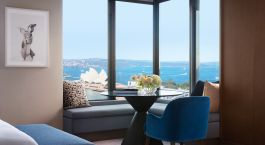 Blick auf ein Wohnzimmer mit blauen Wänden und einem großen Fenster