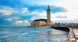 ein großer Uhrturm neben einem Gewässer