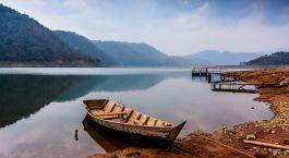 ein kleines Boot in einem Gewässer mit einem Berg im Hintergrund