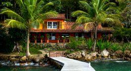 ein Pool neben einem Gewässer, umgeben von Palmen