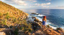 eine Person, die auf einem Felsen neben einem Gewässer steht