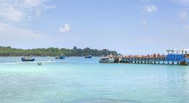 ein blau-weißes Boot, das neben einem Gewässer sitzt