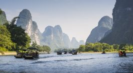 a small boat in a body of water with Li River in the background