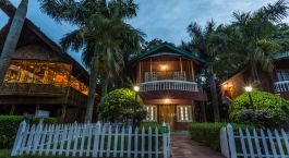eine leere Parkbank neben einer Palme vor einem Haus