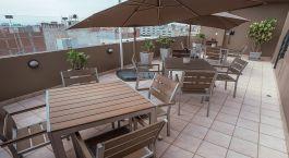 Sitzbereich mit Bu00e4nken, Tischen und Sonnenschirmen im Wyndham Costa del Sol Chiclayo, Peru