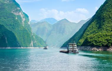 ein kleines Boot in einem Gewässer mit Qutang-Schlucht im Hintergrund