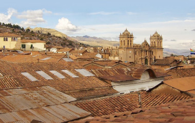 Twin towers and dome of the historic Iglesia de la Compania seen across the red rooftops of Cusco in Peru, South America